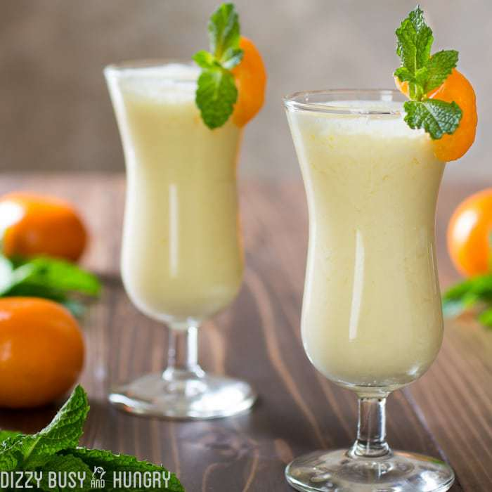 Front view of two smoothie glasses filled with pineapple orange smoothie and garnished with orange wedges and mint. Oranges and mints surround the glasses