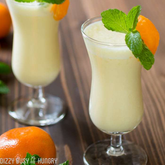 Closeup view of two smoothie glasses filled with pineapple orange smoothie and garnished with orange wedges and mint. Oranges and mints surround the glasses